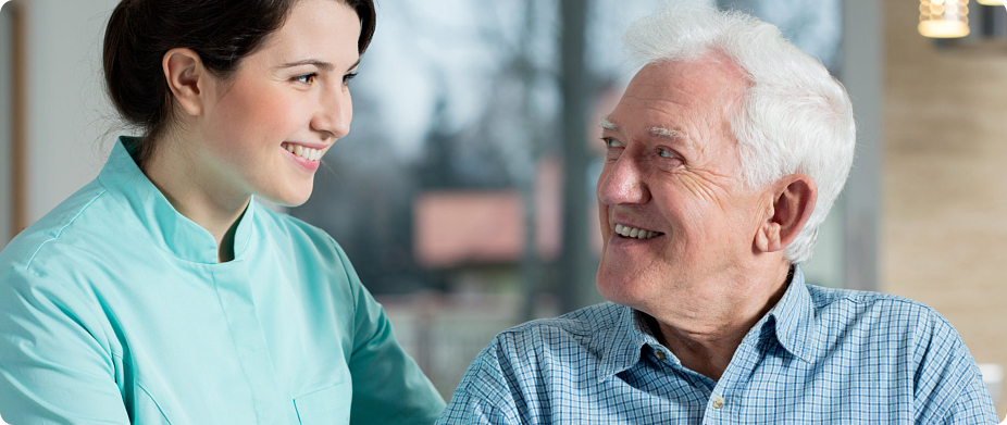 caregiver and patient looking at each other while smiling